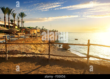 Sandy beach in egyptian hotel at sunset - Stock Photo