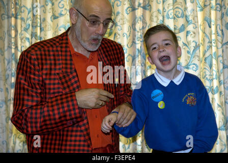 Youngster having fun with a magician at a Macmillan Cancer Care fundraising day, Liphook, Hampshire, UK. - Stock Photo