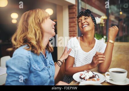 Two multiethnic young female friends enjoying coffee together in a restaurant laughing and joking while touching - Stock Photo