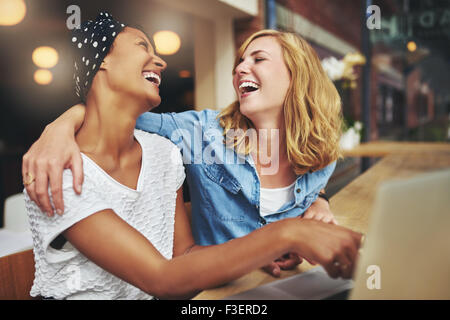 Two affectionate multiracial women friends hugging and laughing as they point at a laptop computer screen that they - Stock Photo