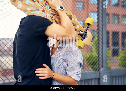 caressing couple hiding behind skateboard and kissing - Stock Photo