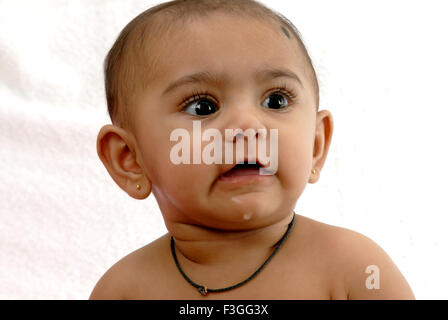 South Asian Indian baby ; naughty expression ; looking at side ; white background ; India MR#152 - Stock Photo