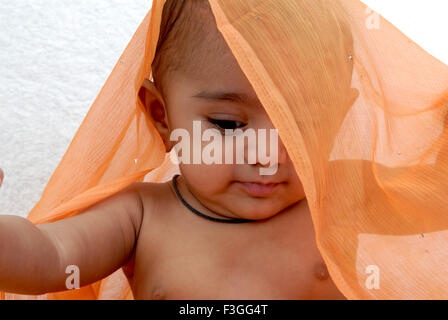 South Asian Indian baby ; with naughty expression ; looking down ; orange color semi transparent cloth covered her - Stock Photo