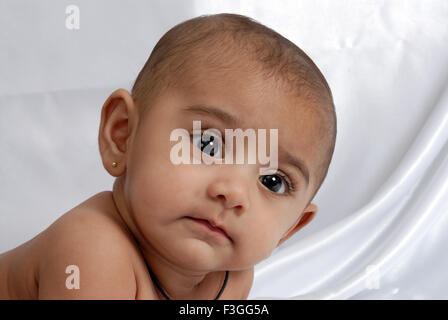 South Asian Indian baby ; naughty expression ; looking at side ; white background; India MR#152 - Stock Photo