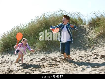 Girl and boy playing with orange sports bat and tennis ball on dunes - Stock Photo
