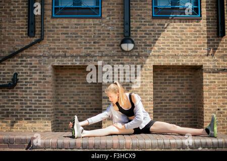 Runner stretching on walkway, Wapping, London - Stock Photo
