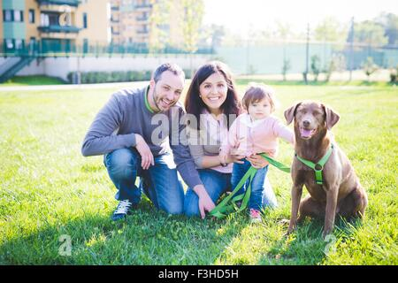 Portrait of mid adult couple with toddler daughter and dog in park - Stock Photo