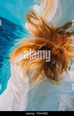 Young red headed woman underwater, overhead view - Stock Photo