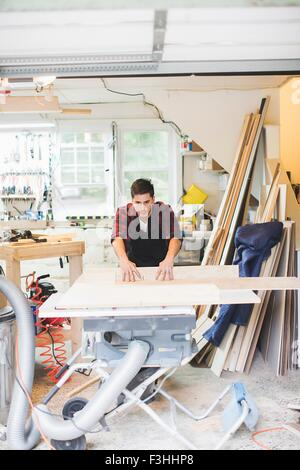 Young man in workshop wearing apron using table saw to cut wood - Stock Photo