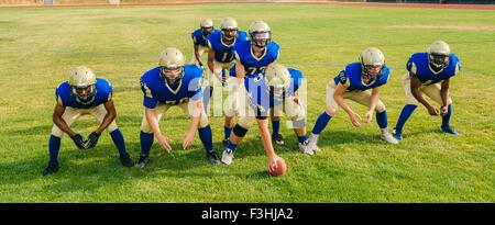 Team of teenage and adult American football players hunkering down on pitch - Stock Photo