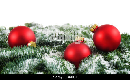 Simple Christmas arrangement with red baubles on snow-covered fir twigs, studio shot isolated on white background - Stock Photo