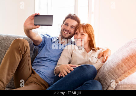 Happy couple in love taking a selfportrait with a cell phone. Home sofa. Lens flare - Stock Photo