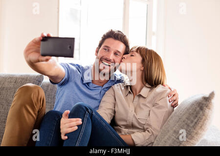 Couple in love taking a selfie with a mobile phone. it makes him a kiss - Stock Photo