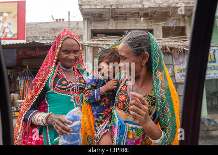 Rajasthani women wearing traditional costumes showing a child to a tourist in a taxi. - Stock Photo
