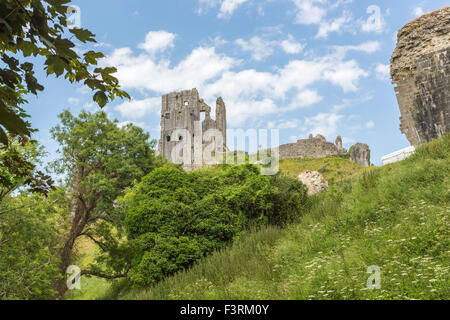 The hilltop ruins of Corfe Castle in Corfe, Dorset, south-west England on a sunny day with blue sky - Stock Photo