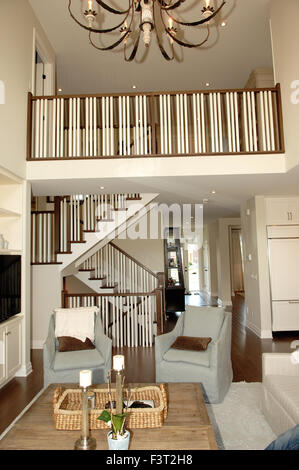 A big elegant living room and hallway and staircase too second floor with light fixture and table. - Stock Photo
