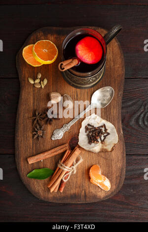 Glass of mulled wine (punch) in glass-holder served on wooden plate with spices over dark wooden table. Top view - Stock Photo