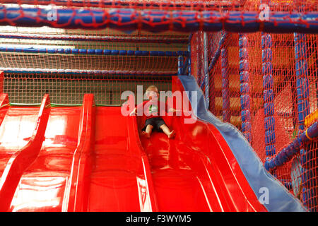 Young boy coming down slide in playbarn - Stock Photo