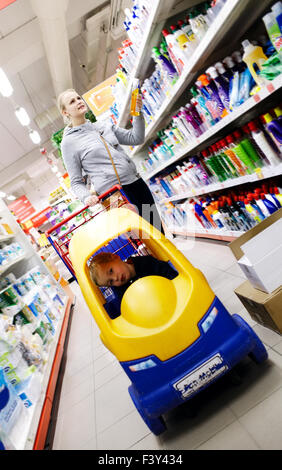 Mother and son shopping in a supermarket - Stock Photo