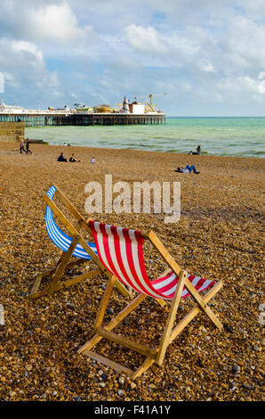 Two deckchairs on the single beach at Brighton and Hove with Brighton Pier in the distance, East Sussex, England. - Stock Photo