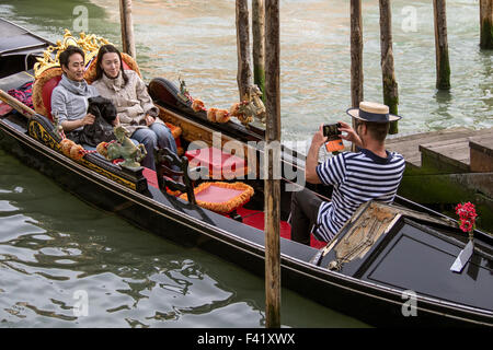 Gondolier taking photo for passengers Gondolas on the Grand Canal in Venice - Stock Photo