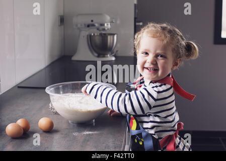 Little girl mixing batter, smiling, portrait - Stock Photo