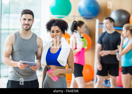 Client and trainer looking at tablet pc - Stock Photo