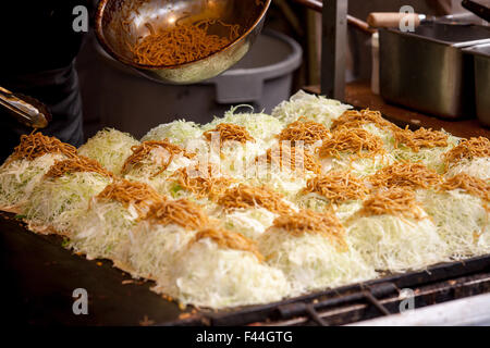 Japanese okonomi-yaki with soba noodles on top of cabbage - Stock Photo