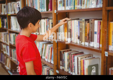 Side view of boy selecting book in library - Stock Photo