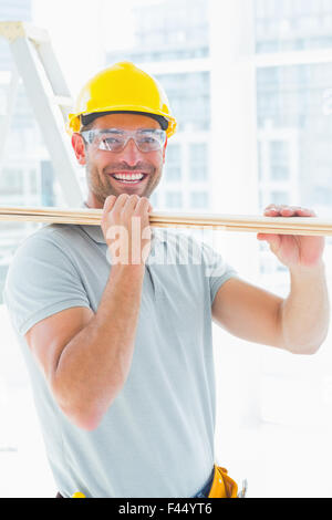 Happy carpenter carrying wood in building - Stock Photo