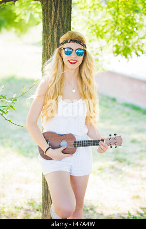 Knee figure of young handsome caucasian long blonde straight hair hippy woman posing leaning against a tree in a - Stock Photo