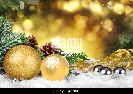 Glamorous Christmas scene with gold ornaments, fir branches and pine cones on snow and defocused shiny golden lights - Stock Photo