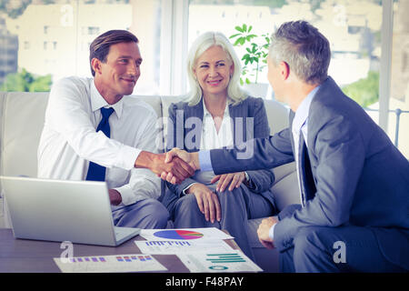 Business people shake hands on couch - Stock Photo