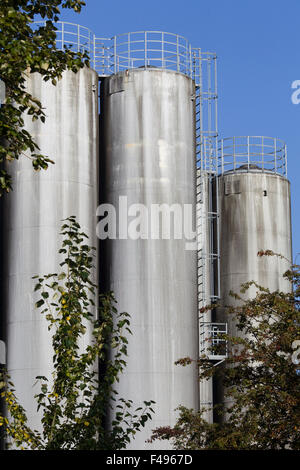 Giant silos with ladders against a blue sky - Stock Photo
