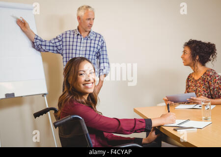 Businesswoman on wheelchair writing in book - Stock Photo
