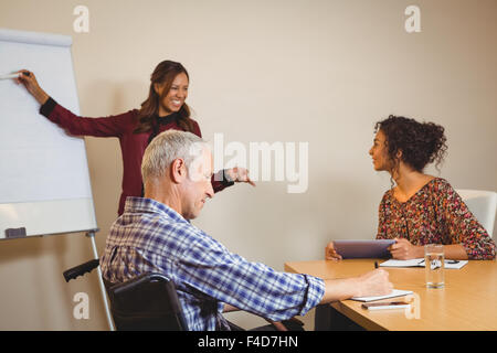 Businessman on wheelchair writing in book - Stock Photo