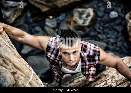 Three Quarter Shot of an Attractive Athletic Young Man Climbing a Rock at the River or by the Sea or Ocean - Stock Photo