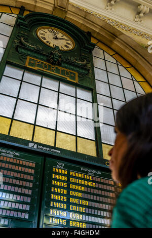 Woman reads the train schedule board in Porto's famous Sao Bento railway station. September, 2015. Porto, Portugal. - Stock Photo