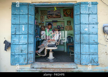 Pushkar, India-March 22, 2014:Unidentified local people in the berber shop in the street of Pushkar. - Stock Photo
