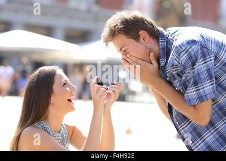 Proposal of a woman asking marry to a man in the middle of a street - Stock Photo