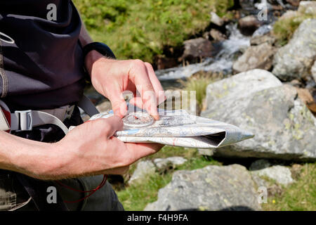 Hiker taking a bearing using a hiking map and compass for navigating a right direction in British mountains seen - Stock Photo