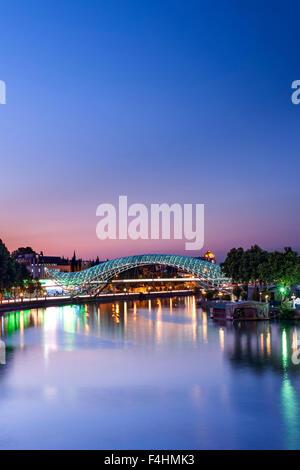 Dusk view of the Bridge of Peace, a pedestrian bridge spanning the Mtkvari River in Tbilisi, the capital of Georgia. - Stock Photo