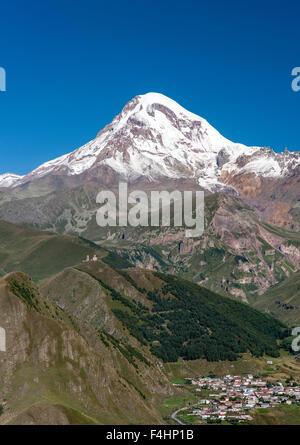 Mount Kazbek (5047m), the village of Gergeti and Gergeti Trinity Church in the Caucasus Mountains of northern Georgia. - Stock Photo