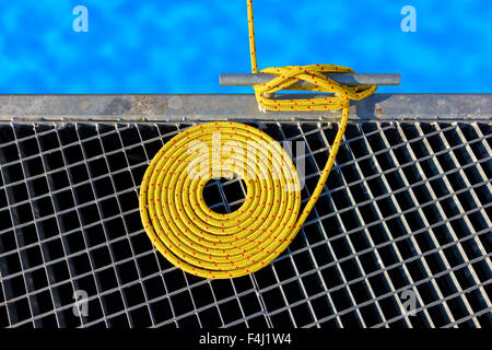 Marine background made of mooring rope with a cleat on a pier. - Stock Photo