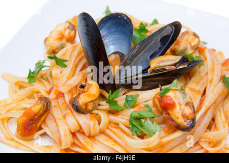 Pasta with mussels on white background close up view - Stock Photo