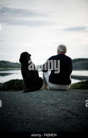 Sweden, Bohuslan, senior man with dog relaxing near lake - Stock Photo