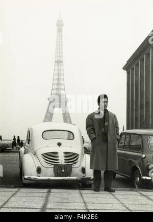Japanese man close to a car with the Eiffel Tower in the background, Paris, France - Stock Photo