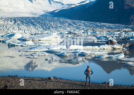 Person beside Fjallsarlon iceberg lagoon, beneath Fjallsjokull glacier. Vatnajokull National Park, Sudhurland, Iceland. - Stock Photo