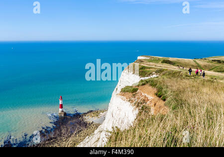 Walkers on the clifftop path overlooking the lighthouse at Beachy Head, near Eastbourne, East Sussex, England, UK - Stock Photo