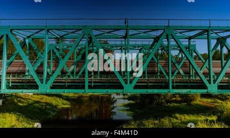 Train passing on the metal railway bridge through the small river - Stock Photo